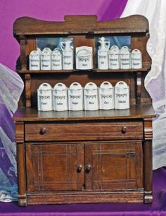 """DOLL-SIZE ANTIQUE WOODEN SIDEBOARD & GERMAN PORCELAIN CANISTER SET. Sideboard 16"""" W. x 21"""" H. Dark wood, high curved back, two upper shelves and two mirrors, one drawer and two lower doors, carved details and wooden pulls; German white porcelain canister set with gilt trim and lettering comprised of twelve lidded canisters for spices, grains, coffee and tea, lidded salt box, vinegar and oil cruets."""