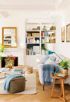 Salón blanco y luminoso con suelo de parquet en espiga. Destaca su  llibrería de balda 26161ae0687