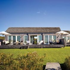 The homeowner added a trio of white market umbrellas for shade and a wicker patio set to this updated deck. | Coastalliving.com