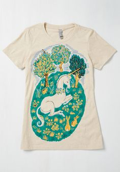 <p>With a graphic as whimsical as that of this unicorn-printed T-shirt, how could you possibly pass it up? Lush trees, marigold rabbits, and soft green grass frame the horned heroine of this cotton-blended top, creating an imaginative look that just can't be tamed!</p>