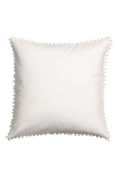 Cushion cover with pompom trim: Cushion cover in a cotton weave with a pompom trim around the edges and a concealed zip.