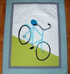 bike quilt- do with a navy blue boarder, light blue sky, dirt color ground, black tiers, and a red tandom.