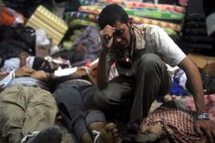 A young man mourns next to the bodies of protesters killed during the clearing of one of the two sit-ins of ousted president Morsi supporters, at the field hospital, near Rabaa Adawiya mosque, Cairo, Egypt, August 14.(Mosaab Elshamy/European Pressphoto Agency)