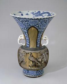 Anonymous | Vaas met een vogelkooi, Anonymous, c. 1700 - c. 1720 | Vaas met wijd uitlopende hals en met twee kleine oren gemodelleerd in de vorm van olifantskoppen. Als bolle buik een vogelkooi rond de vaas, gemaakt van gelakt hout en metaaldraad. In de kooi bloemen en twee vogels, staand op rotsen en takken. De vaas is beschilderd in onderglazuur blauwondergalzuur blauw met bloemranken waarin vier staande lambrequins zijn uitgespaard, gevuld met geomtrische patronen in reliëf en met goud…