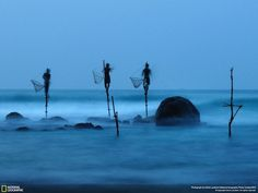 Honorable Mention People Category | Photo and caption by Ulrich Lambert  Stilt fishing is a typical fishing technique only seen in Sri Lanka. The fishermen sit on a cross bar called a petta tied to a vertical pole planted into the coral reef. This long exposure shot shows how unstable their position is.