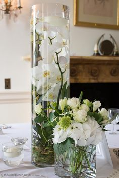 White Orchids with roots and floating candles in a tall vase. An elegant wedding table centre design at North Cadbury Court. As top UK wedding florists, The Wilde Bunch love styling this venue for our London clients and guarantee a totally original design for every Bride. Wedding Table Centres, Country House Wedding Venues, London Bride, Beautiful Table Settings, Table Centers, White Orchids, Tall Vases, Floating Candles, Florists