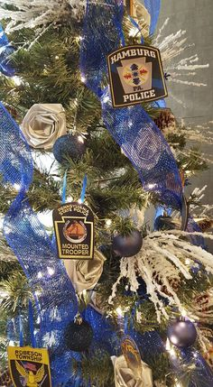 Crime Alert of Berks County Christmas Tree in the lobby of the Double Tree Hotel. Designed and trimmed with off white hand made silk roses and a variety of police badges from around Pennsylvania designed & donated by Kurtz Florist, Hamburg,  PA.