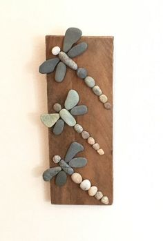 Adorable dragonflies made of rocks on driftwood. Featuring: handpicked local rocks beautifully aged driftwood hanging hook on back can be hung indoors or outdoo
