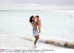 Mother and toddler daughter paddling in sea, Tuscany, Italy