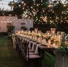Love long wooden rustic tables and the varying size hurricane candles... mixed with strung lights makes for a romantic outdoor setting