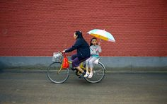 A girl holds an umbrella while sitting on the back of mum's bicycle on a road in Beijing