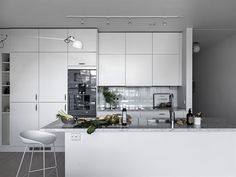 Istället för kakel täcks väggen vid arbetsytan av ett stänkskydd i vitt glas. Här finns gott om förvaring i flera praktiska skåp och kökslådor | Ballingslöv