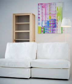 A graphic painting hangs above a white sofa with pillows the same colors as the painting.