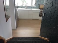 Coming down newly dark carpeted stairs from living room into kitchen with glass cabinet to left