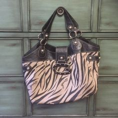 """Guess shoulder bag  Authentic signature guess shoulder bag with canvas body in zebra print and framed in leather with leather handles. Flap over magnetic closure on top. Lining in good condition with multiple zippered compartment and slots. Silver hardware. Some wear on handles as shown in pic.  10"""" x 16"""" with comfortable 9"""" shoulder drop. Guess Bags Shoulder Bags"""