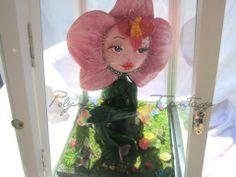 orchid giant made ​​entirely by hand in polymer clay and painted with acrylics air, the greenhouse is made of glass, wood and aluminum