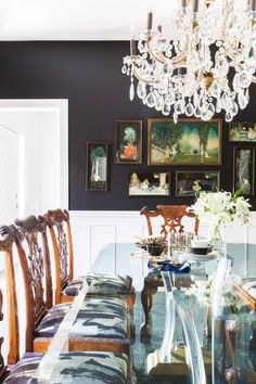Formal dining space with dark gray walls, vintage art, a glass dining room table, vintage reupholstered chairs, and a chandelier