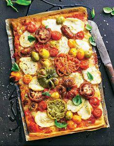 Ohne Pizza geht's nicht? Dann bereitet diese sommerliche Garten-Pizza zu: vegetarisch gut aufgelegt mit Tomaten, Oliven, Basilikum und doppelt Käse - Parmesan für drunter, Halloumi für drüber.