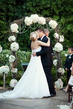 Arch. No flowers and purple/blue fabric or ivory with a table for the sand ceremony