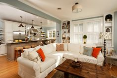So many things to enjoy about this space. The blue paint color goes well with the bright white cabinets & sectional, in addition to the white the pops of orange make the blue stand out even more. The rustic touches of the light fixtures & coffee table go great with the bright stainless steel appliances.
