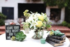 """Flowers in the bride's bouquet are mirrored throughout the table centerpieces, and green English pottery adds a playful element to the """"well wishes"""" table. PHOTOS BY VINE & LIGHT PHOTOGRAPHY"""