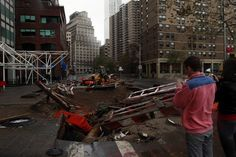 People stand by a hole that has formed at construction site on south street seaport in Manhatan , New York