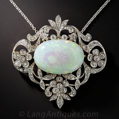 A lovely pastel hued white opal cabochon, weighing 5.50 carats, is elegantly framed in characteristic Edwardian splendor by sparkling diamond-set garlands and floral motifs hand crafted platinum over 18 karat yellow gold. The pendant measures 1 3/8 inches in both directions. Enchanting. Chain is an 18 inch platinum contemporary chain.