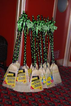 """hand-painted brooms as party favors tied with green and black ribbon complete with  custom made tag encouraging guests to """"Defy Gravity"""""""