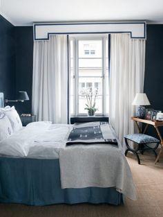 Inred med mörka väggar och ljusa textilier för en ombonad hotellkänsla