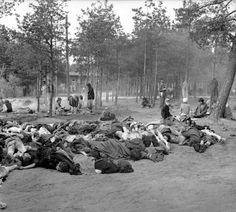 Newly liberated female inmates of Bergen-Belsen concentration camp sit amongst the unburied corpses of fellow camp inmates who perished from starvation and disease in front of Block 210 with Block 209 (Großes Frauenlager) visible through the trees....
