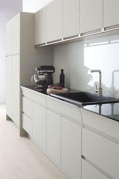 Zoom sur un linéaire de meubles de cuisine Alice d'Arthur Bonnet. Notons l'élégance du plan de travail en verre noir.
