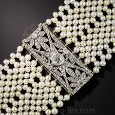 "This iconic Edwardian ""dog-collar"" choker necklace - circa 1910 - sparkles with four matched platinum and diamond spacers (one concealing the clasp) designed in a charming geometric floral motif and joined by intricately woven seed pearls. A romantic and ravishing Belle Èpoque treasure bearing French hallmarks. The satiny white pearls are newer.1 1/4 inch wide by 13 3/4 inches long."