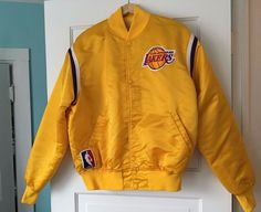 Vintage/80s LA Lakers shiny yellow Starter jacket. Interior is quilted. Two front pockets. Snap button closure. Small flaw on left sleeve--see pictures. Size large. Approximate measurements:Shoulder to shoulder: 22""