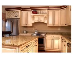 This is a traditional-style custom kitchen remodel from Clarksville, Maryland. Everything was relocated except for the sink. The cabinets are maple wood with crystal white stain and a coffee glaze on presidential mitered doors. Countertops were replaced with a medium tone granite. Custom features include the arched range hood with corbels, wine rack above the fridge, and a custom island. ~ Renewed and Customized by Kitchen Saver Antique White Kitchen with Brown Glaze