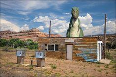 Remains of an abandoned gas station and pumps with a T-rex dinosaur standing guard. Large art décor whimsical photography in as a wrapped canvas / print 11x14 16x20 16x24 20x30 24x36 and 32x48. Image title: Dino's Revenge This image is from my photography series of objects from the past. I photograph many old gas stations and gas pumps and I found this one on a back country road. This image is a composite of two photographs working together to form a more interesting final image. All...