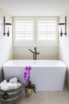 White and tan zen bathroom boasts a nook filled with a rectangular freestanding bathtub paired with an oil-rubbed bronze gooseneck tub filler tucked under windows dressed in plantation shutters lit by oil-rubbed bronze up-light sconces.