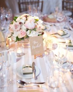 Tea lights surrounded clear glass vases that held centerpieces of roses, hydrangeas, and peonies. Check out more of this rustic wedding in the English countryside!