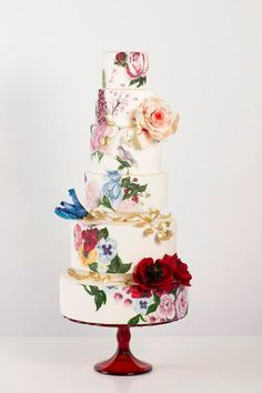 Loving the hand painted flowers with touches of red on this 6 tier wedding cake by Nadia & Co.