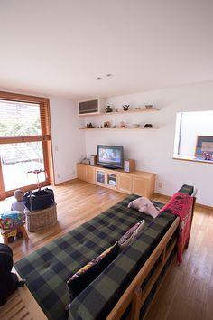 ナラ材の床と白い壁が気持ちいい、広々としたリビング。大型のソファもこの家では小さく見える。