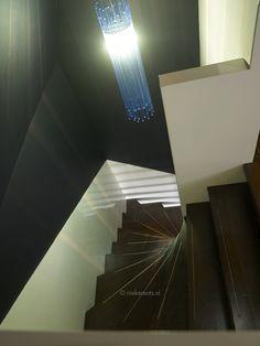Door de vergrijsde kleuren staat de lamp centraal bij deze trap. Door de het schuine dak en de verschillende lijkt het alsof er een 3 hoek in de muur zit.