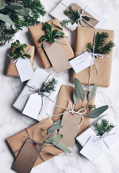 brown paper packages with greenery and twine. / sfgirlbybay