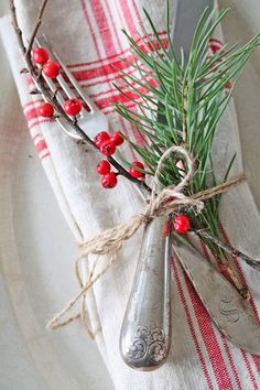 Vintage red lines for Christmas table. Vintage silverware, greenery and berries.