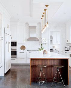 Few things feel as luxurious as a bright, white kitchen. The floor-to-ceiling tile is warmed up with a walnut island and the statement brass hardware and light fixtures are the icing on top. Designed by #TayanKrpan #kitchentuesday #inspiration