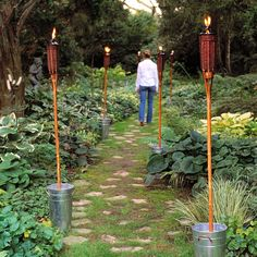 Decking your yard with tiki torches is an inexpensive, festive way to bring island style home -- and to light up the night without electricity. Use them to line a path or surround a patio. If the ground is paved or rocky, you may not be able to find places to poke the torches into the soil. Instead, anchor them in gravel-filled, galvanized-steel flower buckets, and have yourself a tropical night.
