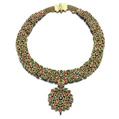 RUBY, EMERALD, ENAMEL AND DIAMOND NECKLACE, INDIA, 19TH CENTURY. Composed of fifteen hinged floral and foliate medallions suspending a matching pendant, set with foiled back cabochon emeralds and rubies, table-cut diamonds and enamel, the border and reverse decorated with polychrome floral enamel, length approximately 380mm, one link brocken and an emerald deficient.