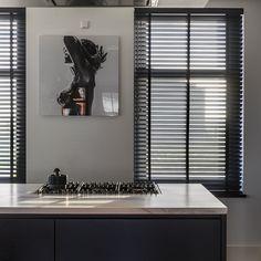 In de donkerbruine keuken met marmeren blad hangen de houten jaloezieën van Zonnelux. Het licht dat tussen de lamellen door schijnt, reflecteert zo op het keukenblad van het kookeiland. Black Blinds, Black Shutters, Curtains With Blinds, Black Kitchens, Kitchen Interior, Home Projects, Interior Inspiration, Home Remodeling, Decor Styles