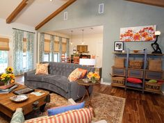 A custom designed sofa takes center stage in this bright open living room. Acacia wood flooring mirrors the wooden ceiling beams and complements the rustic chic coffee table.