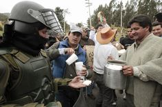 GETTING ALONG: Farmers gave police cheese and sugar water during a protest in La Calera, Colombia, Wednesday. People have been demonstrating against President Juan Manuel Santos's agriculture and economic policies, which farmers say leave them unable to turn a profit. (Jose Miguel Gomez/Reuters)