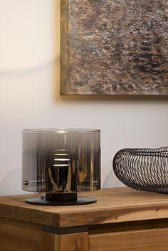 Lampa stołowa OWINO wykonana jest z wysokiej jakości aluminium oraz dymionego szkła. Klosz skrywa jedną żarówkę LED z gwintem GU10, a efekt lustra szklanego cylindra daje iluzję wielu żarówek. Dołączona do zestawu żarówka jest ściemnialna (brak ściemniacza w komplecie).