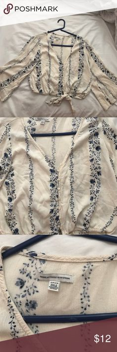 Cropped floral button up blouse Cream colored crop with a sinched waist and bell sleeves. Buttons up the middle with a low cut neck and tie at the bottom. Beautiful navy blue floral stripes. Never worn but has been washed American Eagle Outfitters Tops Blouses